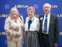 Three people pose for a photo with the LSU Law logo in the background