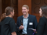 A male student smiles as he talks to two female students