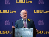 A man in a suit and tie talks at a podium with the LSU Law logo in the background
