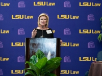 A woman in a black dress talks at a podium with the LSU Law logo in the background