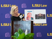 A woman in a black dress holds up a sign with the LSU Law logo in the background