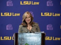 A woman wearing a brown jacket talks at a podium with the LSU Law logo in the background
