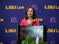 A woman wearing a red dress talks at a podium with the LSU Law logo in the background