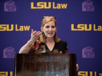 A woman wearing a black and red dress talks at a podium with the LSU Law logo in the background