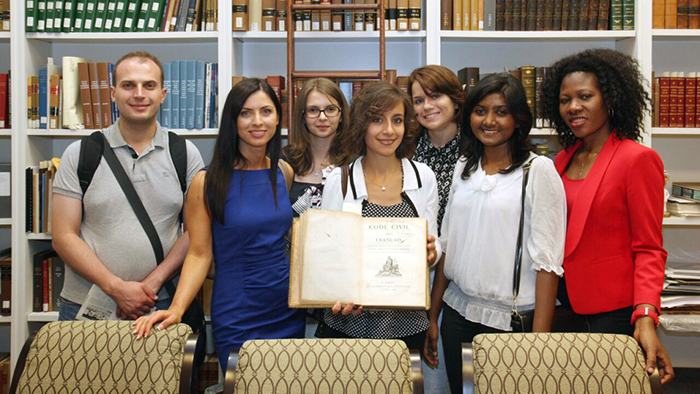 LL.M. students posing at the Lousiana Supreme Court of Justice with an original edition of the Code Civil