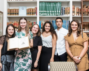 Six French students from the LLM, one of them holding the original edition of the 1804 Code Napoleon