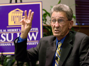 A man holds up three fingers while talking with the LSU Law logo in the background