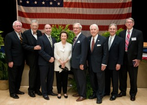 Seven men and one woman wearing suits pose for a photo with an American flag in the background