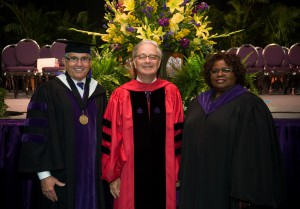 Two men and a woman wearing graduation robe smile for a photo with flowers in the background