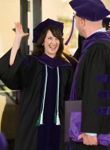 A female wearing graduation gown gives a high-five to another graduate