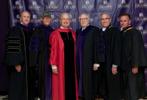 Six men wearing graduation robes smile with the LSU Law logo in the background