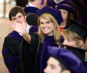 A female graduate wearing a cap and gown smiles and waves