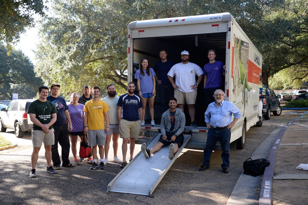 A group of students and faculty pose next to and on a moving truck outside the LSU Law Center