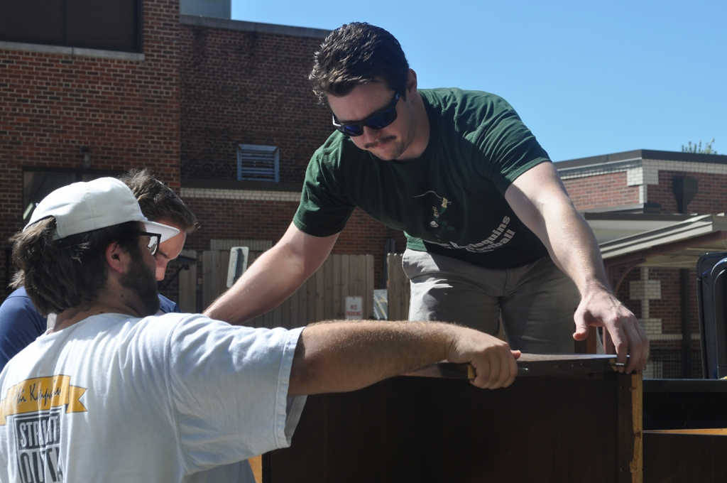Two male students lift furniture onto a truck