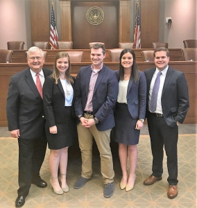 Three men and two women wearing suits pose for a photo with a courtroom in the background