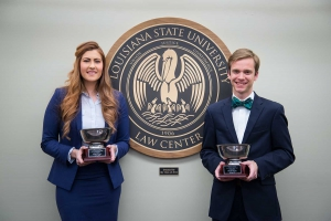 A female and a male student wearing suits hold silver trophies and pose for a photo with the LSU Law Center seal in the background