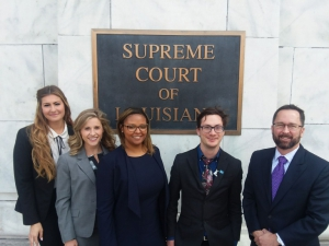 Three female and two males wearing suits pose for a photo with the sign of the Supreme Court of Louisiana in the background