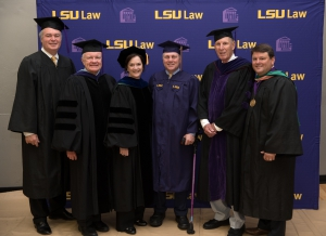 Seven people wearing graduation caps and gowns pose for a photo with the LSU Law logo in the background