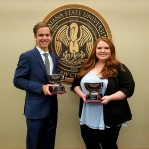 A man and a female wearing suits hold silver trophies with the LSU Law Center seal in the background