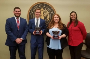 A man and a female wearing suits hold silver trophies and pose with a male and female student with the LSU Law Center seal in the background