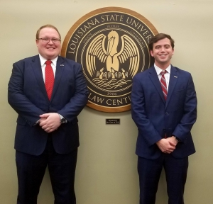 Two male students wearing suits pose for a photo with the LSU Law Center seal in the background