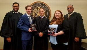 A man and a female wearing suits hold silver trophies and pose with three men in judges' robes with the LSU Law Center seal in the background