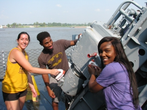 Three students clean part of a warship