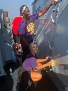 Two students clean part of a warship