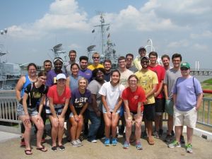 A group of people pose for a photo on a war ship