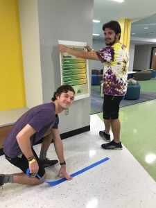 Two male students hang signs and put tape on the floor