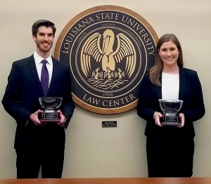 a male and female student pose in front of the LSU Law Center seal holding trophies
