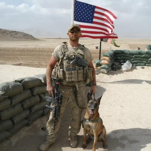 A soldier poses next to a dog with an American flag in the background