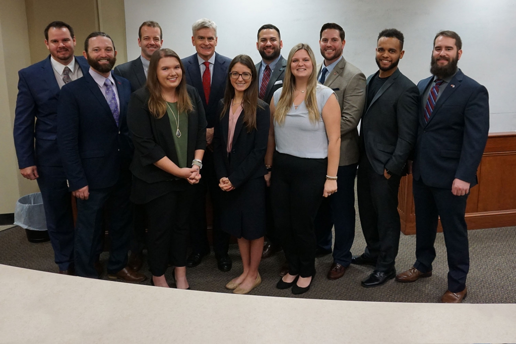 A group of students in suits pose with U.S. Sen. Bill Cassidy