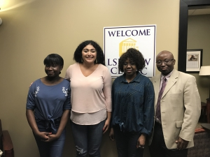 Four people pose for a photo outside the LSU Law Clinic office