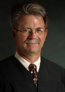 A headshot photo of a man wearing a judge's robe and tie