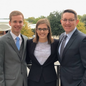 Two men and a woman in suits pose for a photo