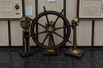 A ship wheel and other instruments with shipping passports in background