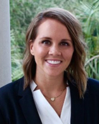 headshot photo of a female in a black suit jacket and white shirt