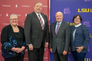 Two men and two women pose for a photo with backdrops of the Centenary College and LSU Law logos in the background