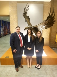 One male and two female students wearing suits pose for a photo in front of an eagle statue