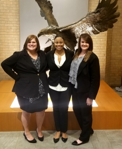 Three female students wearing suits pose for a photo in front of an eagle statue