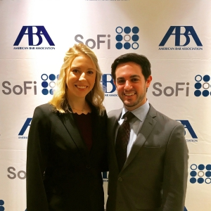 A male and female student pose for a photo wearing suits in front of an American Bar Association sign