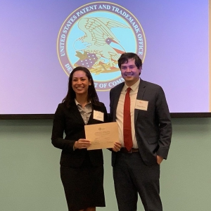 A male and female student pose for a photo wearing suits and holding an award with the U.S. Patent and Trademark Office logo in the background