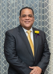 A man in a suit and tie with a yellow boutonniere