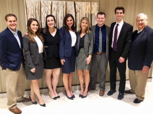 A group of students wearing business attire pose for a photo