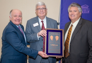 Three men wearing suits and ties hold a wooden plaque and smile for a photo