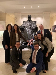 Seven people touch the statue of Judge John Marshall for good luck