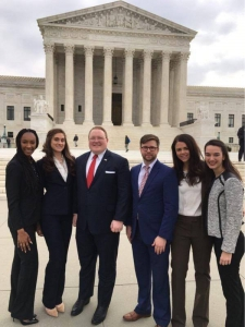Two male and four female students wearing suits pose for a group photo with the US Supreme Court building in the background